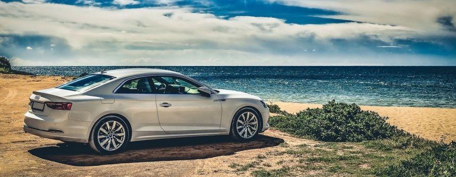 Auto steht am Strand mit Meer im Hintergrund